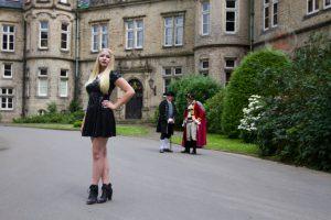 Stolze Frau vor Gebäude mit 2 Barrok gekleideten Herren