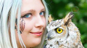 Mädchen mit leuchtend blauen Augen und Eule