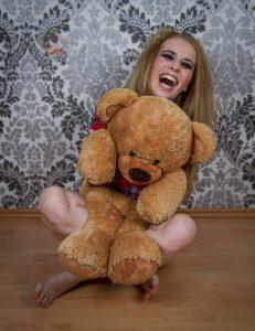 Lachendes Mädchen mit großem Teddybär